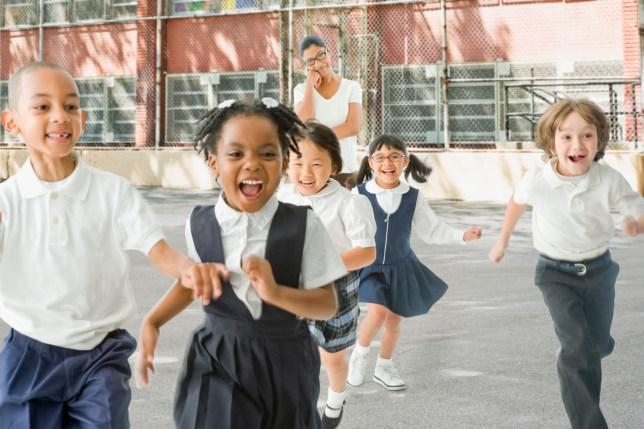 Children running outside a school as half term starts