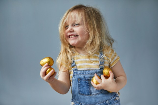 Happy smiling toddler girl holding small chocolate eggs