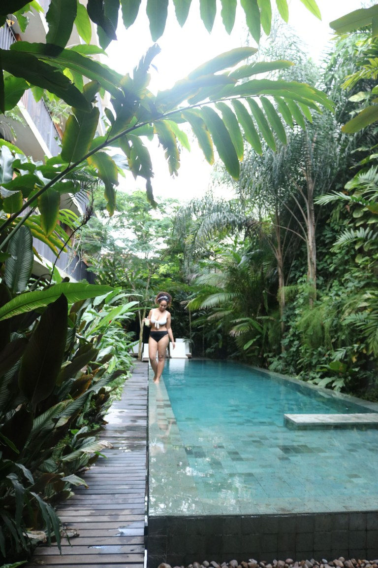 Georgina walking a pool underneath the rainforest's canopy