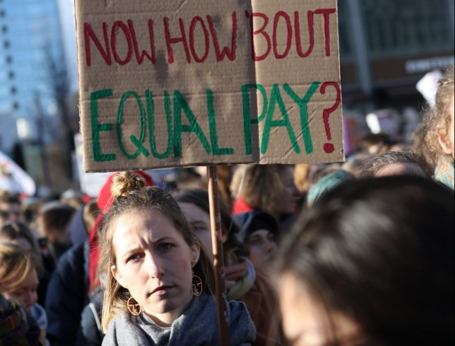 epa07422586 A protestor holds a placard 'Thanks for the Day now how about equal pay?' in a demonstration during the International Women's Day in Berlin, Germany, 08 March 2019. Under the theme 'Think equal, build smart, innovate for change' millions of women worldwide protest for gender equality, more rights and the empowerment of women. Earlier this year he International Women's Day was declared public holiday in Berlin. EPA/FELIPE TRUEBA