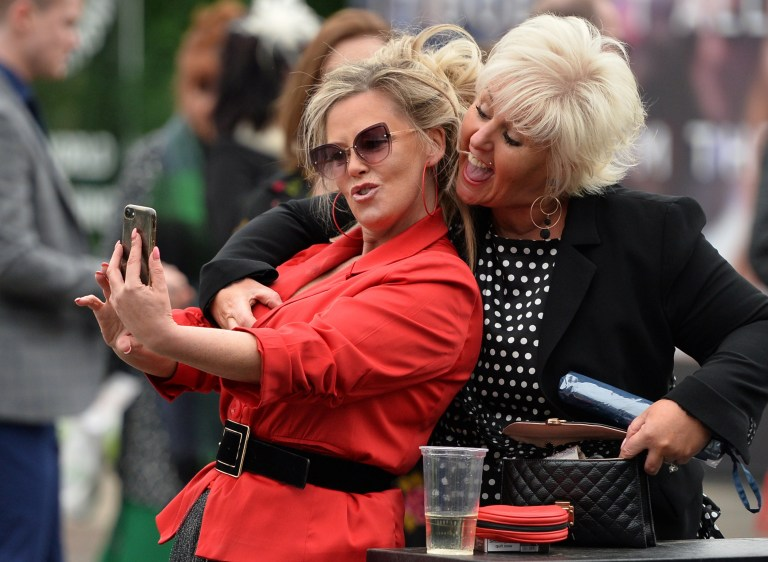 Horse Racing - Grand National Festival - Aintree Racecourse, Liverpool, Britain - April 4, 2019 Racegoers take a selfie during the Grand National Festival REUTERS/Peter Powell
