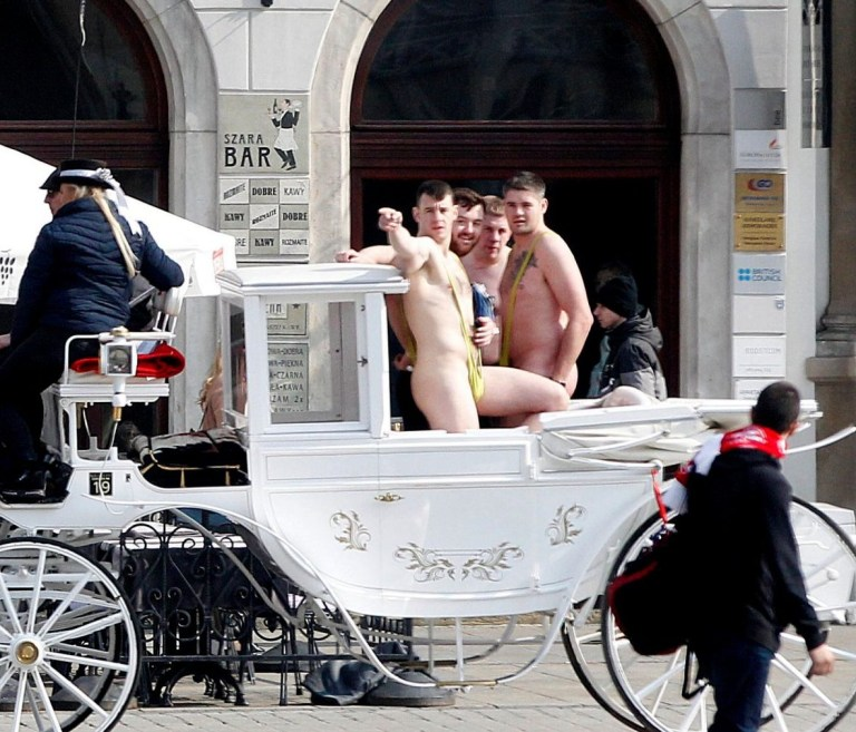 In this photo taken on Friday March 29, 2019, tourists wearing mankinis travel in a horse cab in Market Square in Krakow, Poland. Police in southern Poland say they are investigating four English-speaking tourists spotted last week in Krakow wearing only mankinis, as worn by Borat, the fictional Kazakh alter ego of comic actor Sacha Baron Cohen. If convicted, the men could face up to 30 days in custody or fines of 5,000 zlotys ($1,300) each. (AP Photo/Czarek Sokolowski)