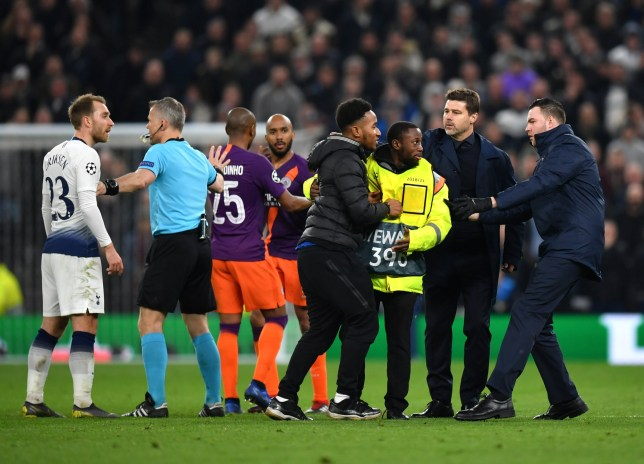 LONDON, ENGLAND - APRIL 09: Mauricio Pochettino, Manager of Tottenham Hotspur attempts to get the pitch invader off the pitch as referee Bjorn Kuipers speaks to Christian Eriksen of Tottenham Hotspur during the UEFA Champions League Quarter Final first leg match between Tottenham Hotspur and Manchester City at Tottenham Hotspur Stadium on April 09, 2019 in London, England. (Photo by Dan Mullan/Getty Images)