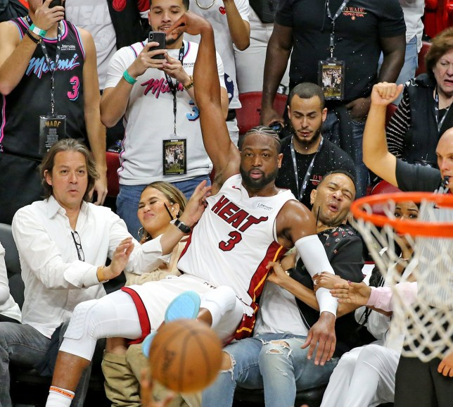 Miami Heat guard Dwyane Wade crushes singer John Legend and his wife Chrissy Teigen after Wade missed a basket in the fourth quarter as they play the Philadelphia 76ers at the AmericanAirlines Arena Tuesday, April, 9, 2019 in Miami. (Charles Trainor Jr./Miami Herald/TNS)
