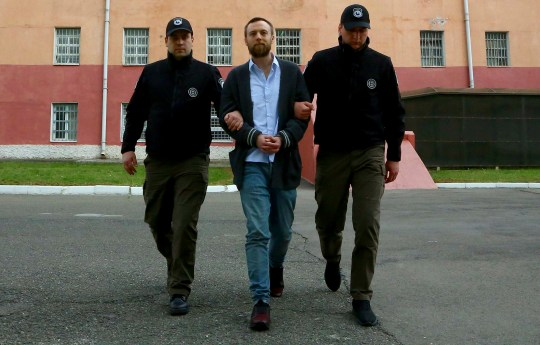 Jack Shepherd, a British man wanted for the manslaughter of a woman killed during a date on a speedboat in London, walks escorted by police in Tbilisi, Georgia, Wednesday, April 10, 2019. Shepherd is set to board a flight to London on Wednesday after a Georgian court ruled last month to extradite him. (Penitentiary Service of Georgia via AP)