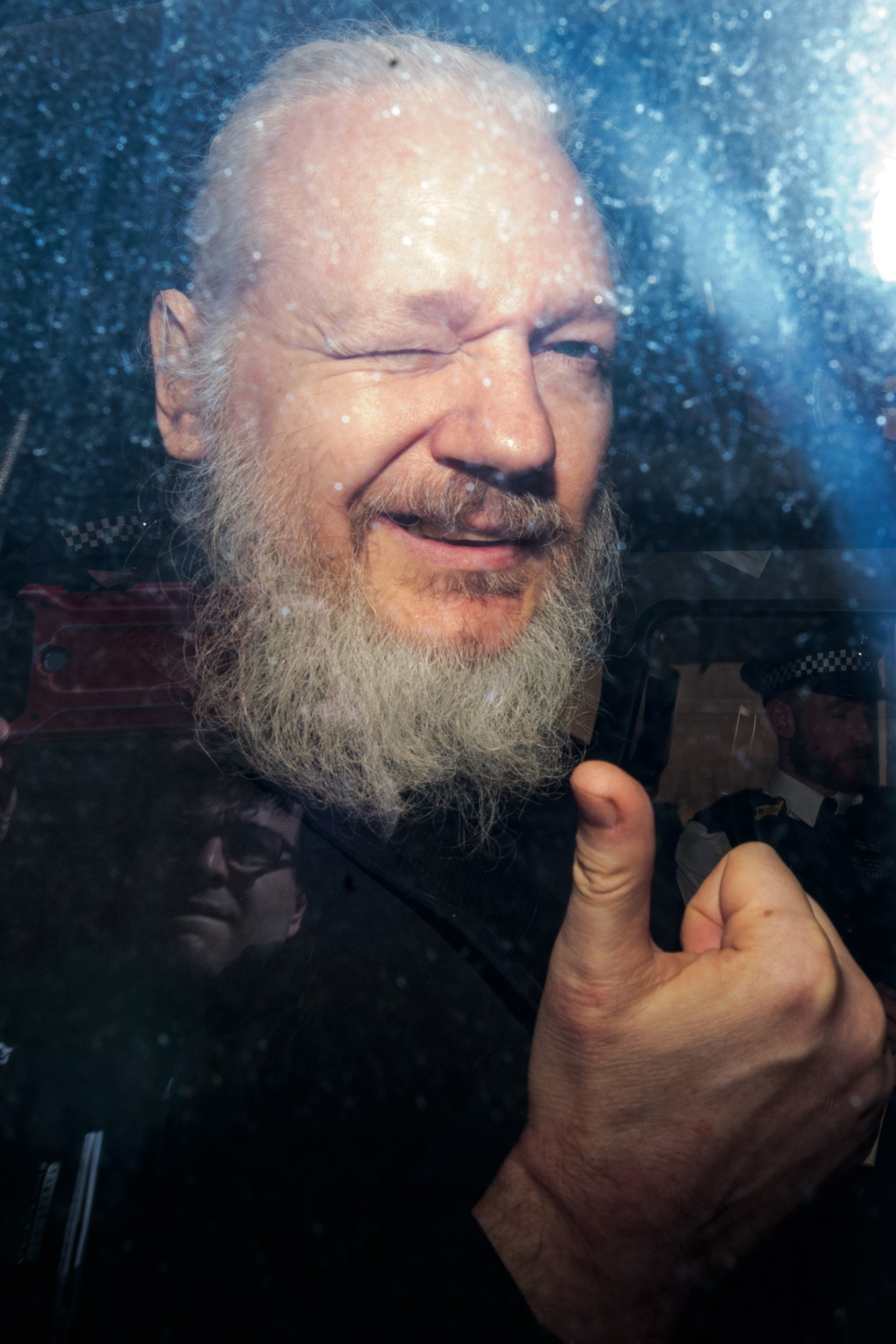 LONDON, ENGLAND - APRIL 11: Julian Assange gestures to the media from a police vehicle on his arrival at Westminster Magistrates court on April 11, 2019 in London, England. After weeks of speculation Wikileaks founder Julian Assange was arrested by Scotland Yard Police Officers inside the Ecuadorian Embassy in Central London this morning. Ecuador's President, Lenin Moreno, withdrew Assange's Asylum after seven years citing repeated violations to international conventions. (Photo by Jack Taylor/Getty Images) ***BESTPIX***