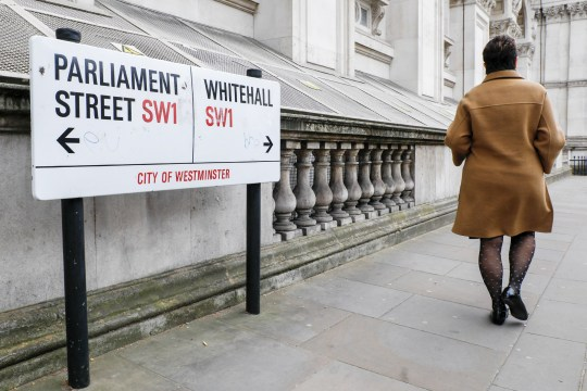 A pedestrian passes a street sign display the start of Parliament Street, left, and Whitehall, right, in the Westminster district of London, U.K., on Wednesday, March 27, 2019. U.K. Prime Minister Theresa May??aims to put her twice-defeated Brexit deal to another vote this week, amid signs some Brexit hardliners might be willing to back it. Photographer: Luke MacGregor/Bloomberg via Getty Images