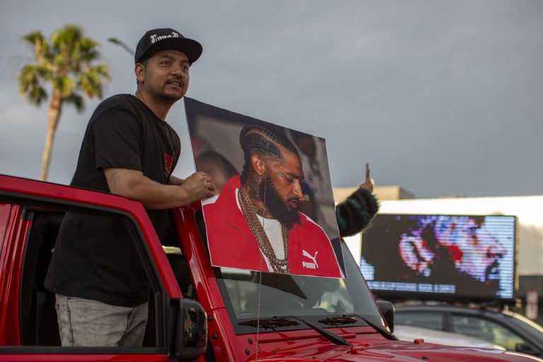 LOS ANGELES, CA - APRIL 11: A man hold a picture of slain rapper Nipsey Hussle from a car in the street near Angelus Funeral Home before the arrival of the funeral procession carrying Hussle on April 11, 2019 in Los Angeles, California. Nipsey Hussle was shot and killed in front of his store, The Marathon Clothing shop, on March 31, 2019 in Los Angeles. (Photo by David McNew/Getty Images)