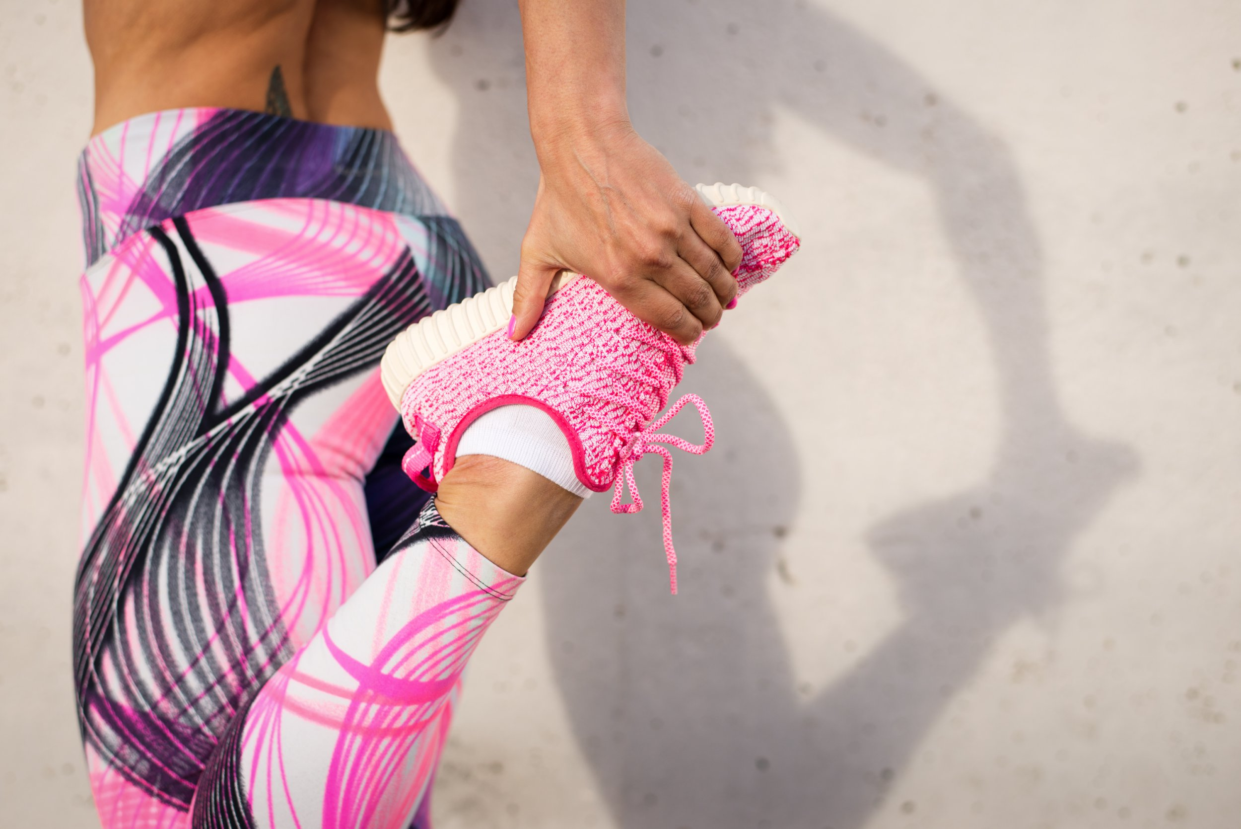 Urban fashion running running sportswear. Female athlete stretching legs after exercising. Healthy lifestyle and sport concept.