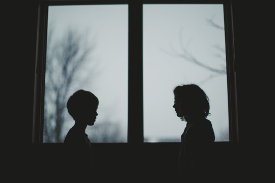 Little boy and little girl stand in front of a window looking at each other creating two silhouettes in of the window with overcast skies behind them.