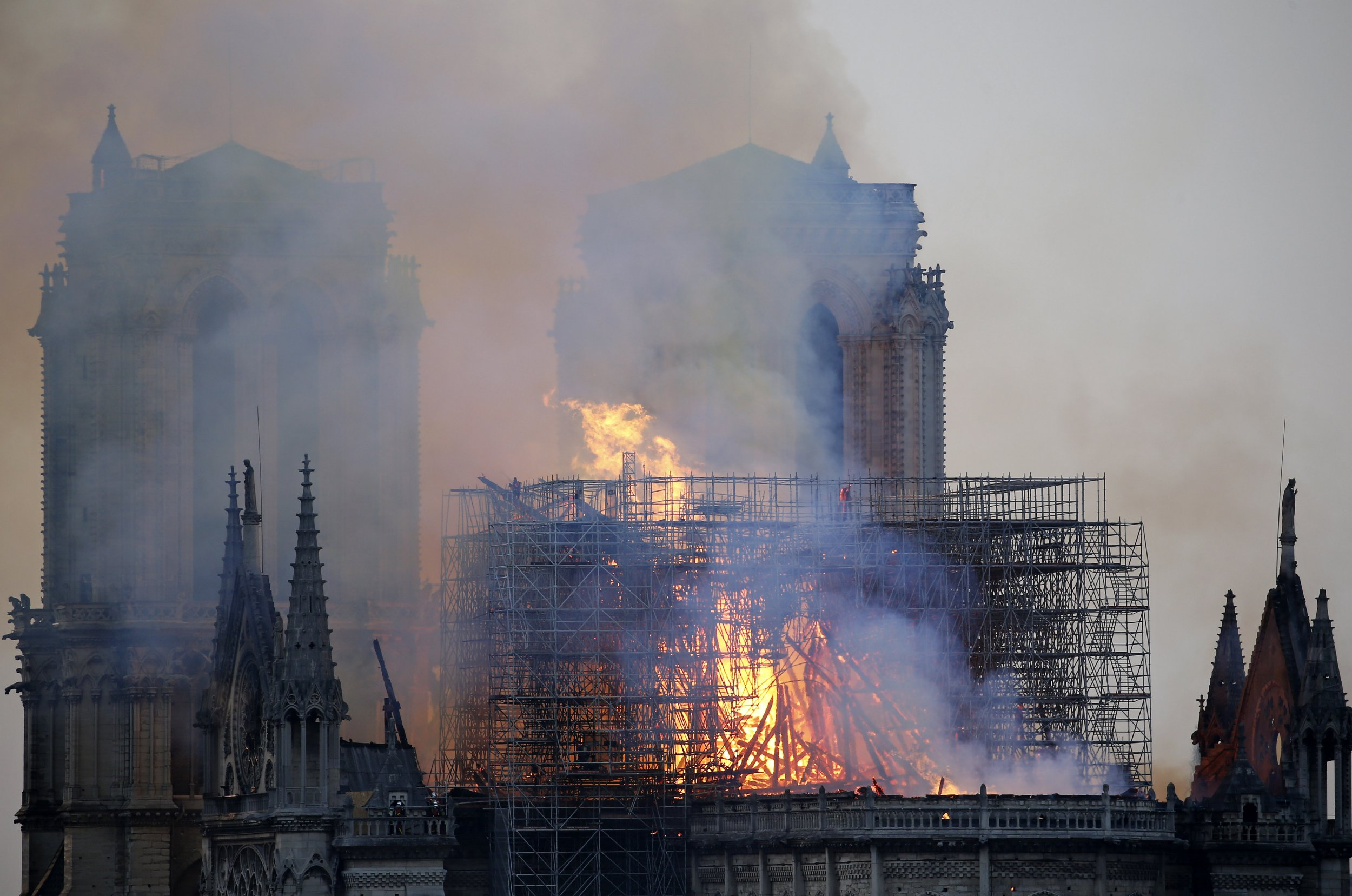 PARIS, FRANCE - APRIL 15: Flames and smoke are seen billowing from the roof at Notre-Dame Cathedral on April 15, 2019 in Paris, France. A fire broke out on Monday afternoon and quickly spread across the building, collapsing the spire. The cause is yet unknown but officials said it was possibly linked to ongoing renovation work. (Photo by Chesnot/Getty Images)