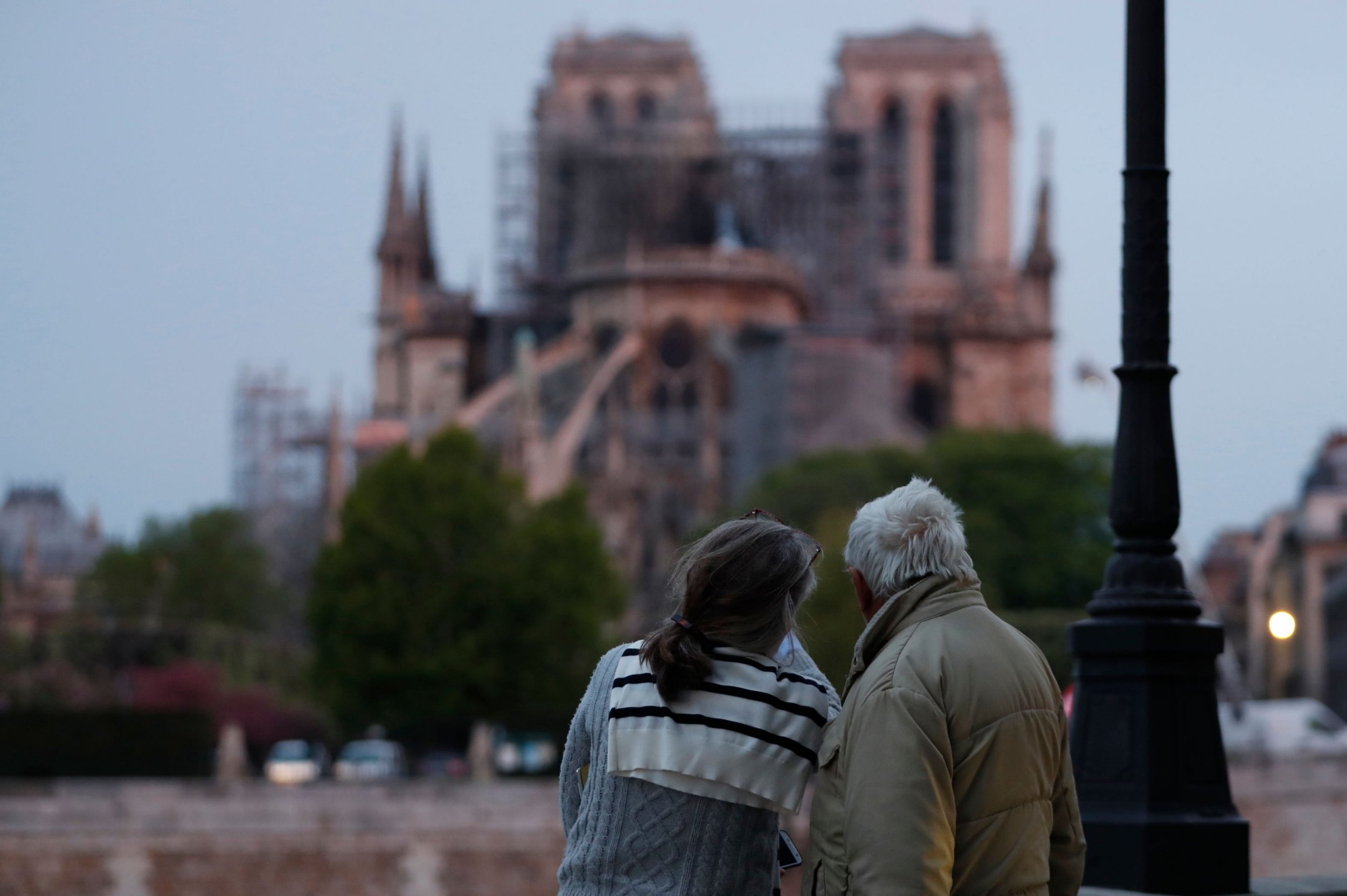 "A couple looks on as firefighters work to extinguish a fire at Notre-Dame Cathedral in Paris early on April 16, 2019. - A huge fire that devastated Notre-Dame Cathedral is ""under control"", the Paris fire brigade said early on April 16 after firefighters spent hours battling the flames. (Photo by Zakaria ABDELKAFI / AFP)ZAKARIA ABDELKAFI/AFP/Getty Images"