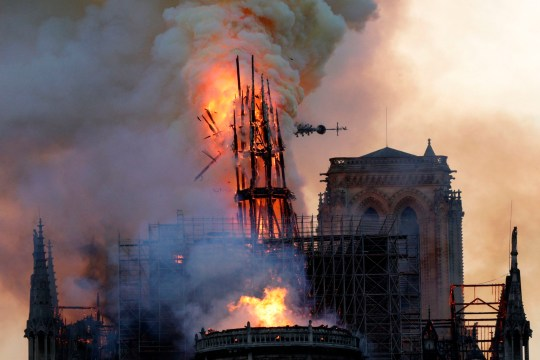 TOPSHOT - The steeple collapses as smoke and flames engulf the Notre-Dame Cathedral in Paris on April 15, 2019. - A huge fire swept through the roof of the famed Notre-Dame Cathedral in central Paris on April 15, 2019, sending flames and huge clouds of grey smoke billowing into the sky. The flames and smoke plumed from the spire and roof of the gothic cathedral, visited by millions of people a year. A spokesman for the cathedral told AFP that the wooden structure supporting the roof was being gutted by the blaze. (Photo by Geoffroy VAN DER HASSELT / AFP)GEOFFROY VAN DER HASSELT/AFP/Getty Images
