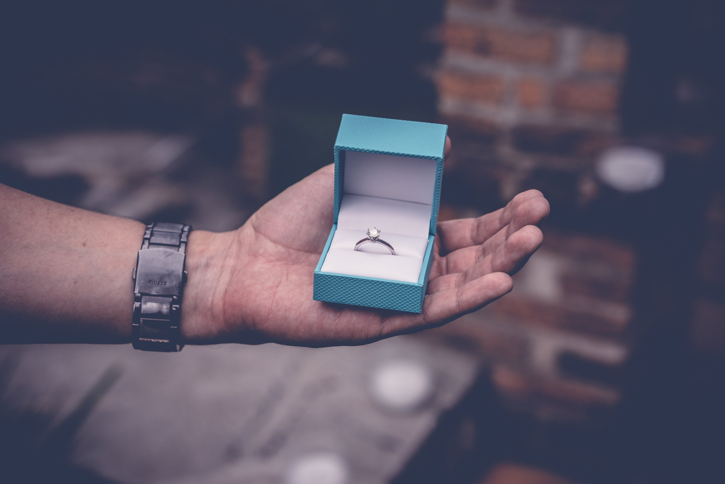 Man holding out engagement ring in blue box