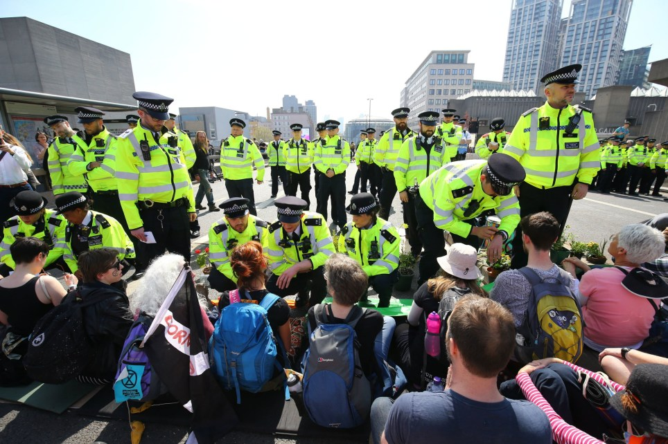 Police talk to Extinction Rebellion demonstrators on Waterloo Bridge in London. PRESS ASSOCIATION Photo. Picture date: Friday April 19, 2019. See PA story ENVIRONMENT Climate. Photo credit should read: Gareth Fuller/PA Wire