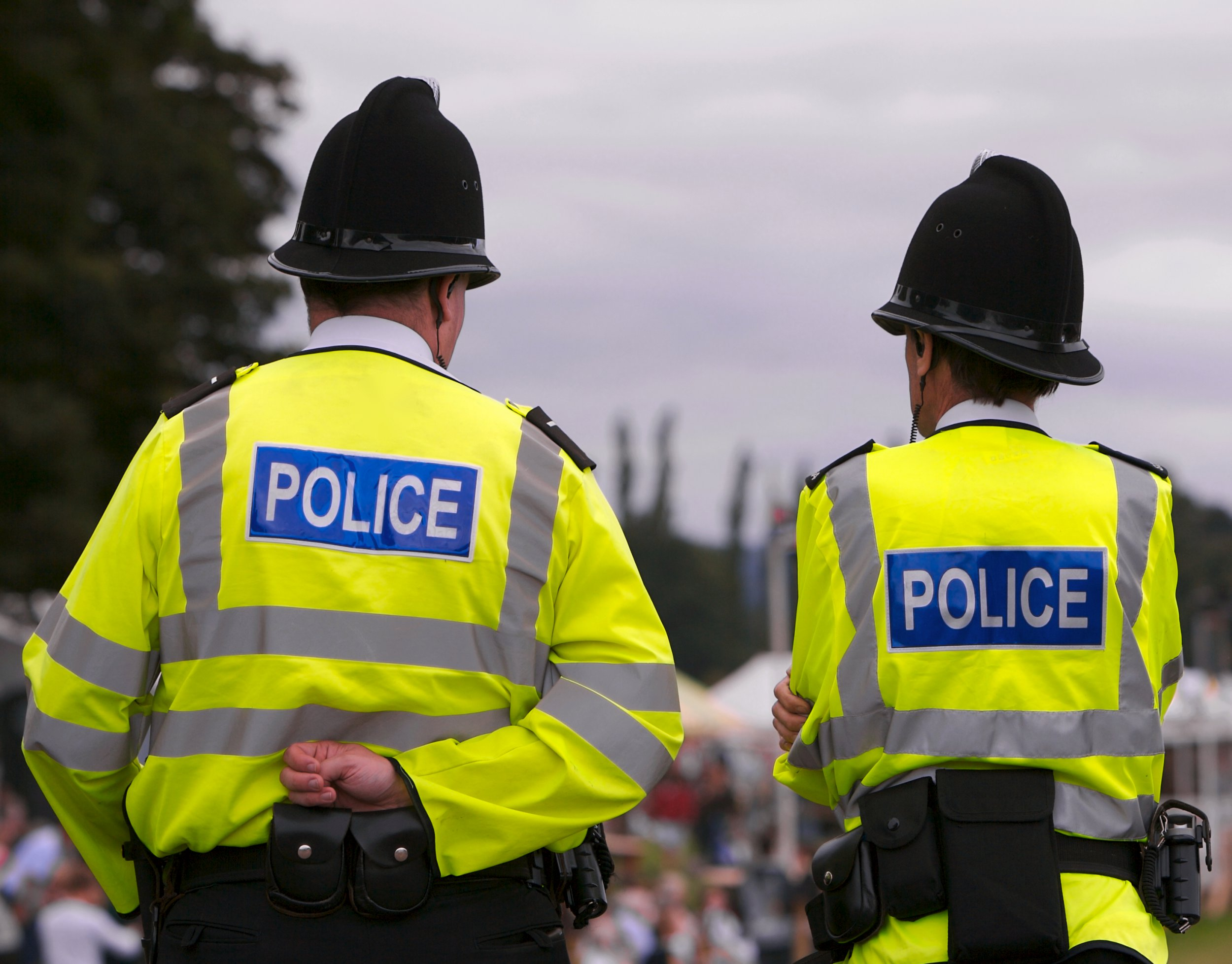 Two British Police Officers guard the entrance to the arena of a Summer Fair, on a typically gloomy British Summers day.