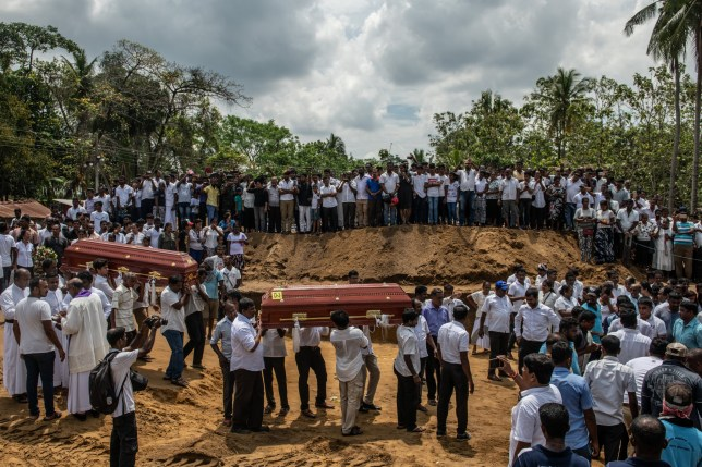 NEGOMBO, SRI LANKA - APRIL 23: Coffins are carried to a grave during a mass funeral at St Sebastian's Church on April 23, 2019 in Negombo, Sri Lanka. At least 311 people were killed with hundreds more injured after coordinated attacks on churches and hotels on Easter Sunday rocked three churches and three luxury hotels in and around Colombo as well as at Batticaloa in Sri Lanka. Sri Lankan authorities declared a state of emergency on Monday as police arrested 24 people so far in connection with the suicide bombs, which injured at least 500 people as the blasts took place at churches in Colombo city as well as neighboring towns and hotels, including the Shangri-La, Kingsbury and Cinnamon Grand. (Photo by Carl Court/Getty Images) *** BESTPIX ***