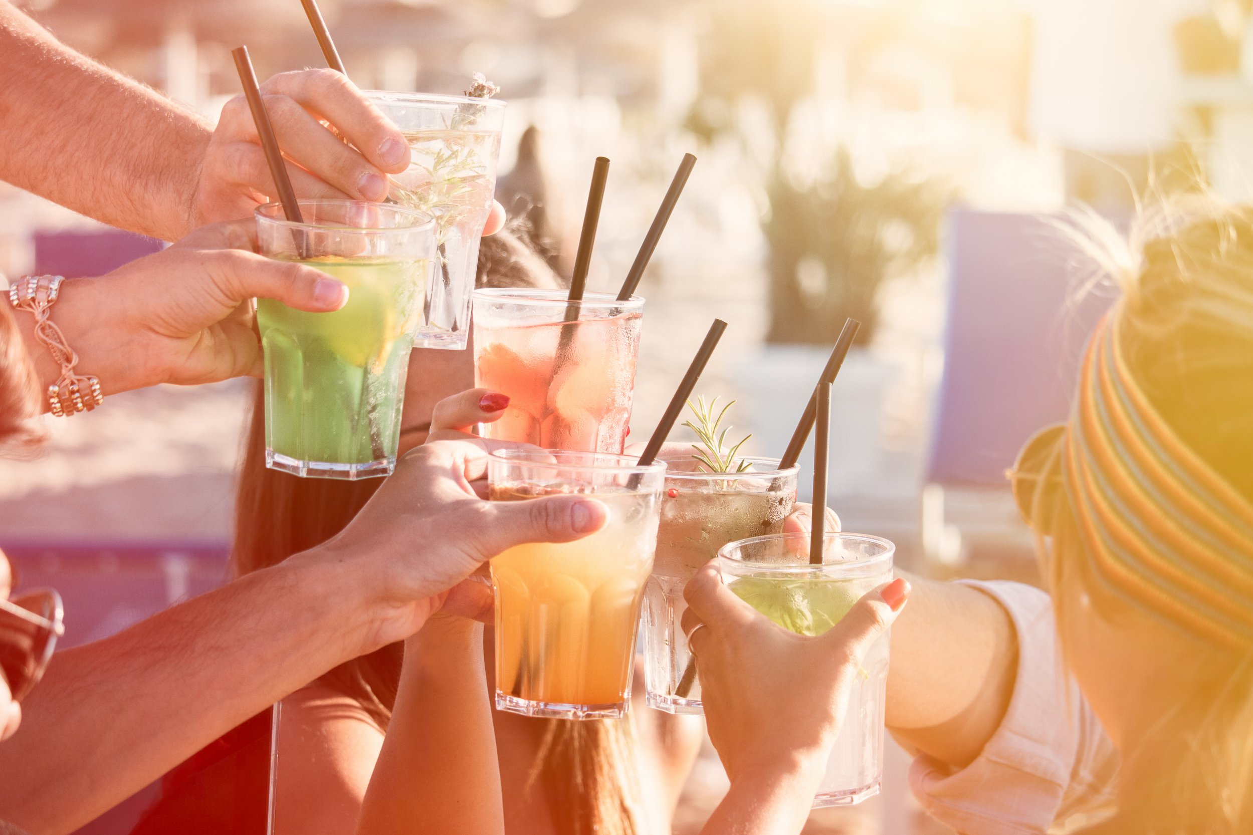 people drinking at party outdoor. group of friends cocktails in hand toasting with glasses.close up on hands and drinks; Shutterstock ID 663056257; Purchase Order: -