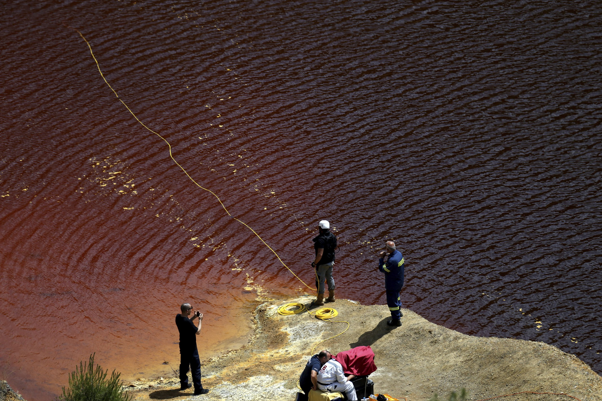 Investigators are searching for bodies with a special camera in a man-made lake near the village of Mitsero outside of the capital Nicosia, Cyprus, Saturday, April 27, 2019. Cyprus police are intensifying a search for the remains of more victims at locations where an army officer, who authorities say admitted to killing five women and two girls had dumped their bodies. (AP Photo/Petros Karadjias)