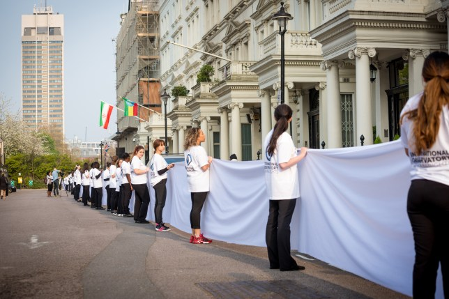 Women standing in front of Iranian Embassy holding large white material