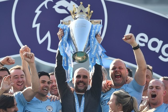 Pep Guardiola lifting the Premier League trophy as Manchester City manager