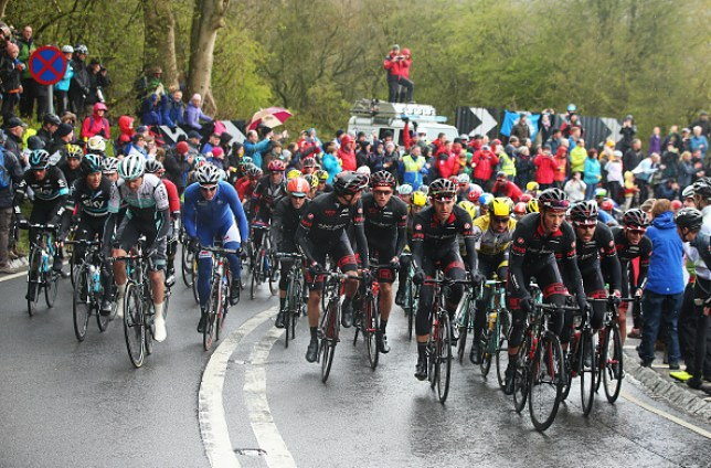 Cyclists riding together as spectators watch in the rain during the Tour de Yorkshire