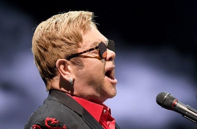 Elton John singing on stage and playing piano