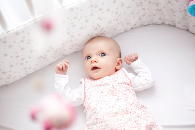 A baby awake in a cot