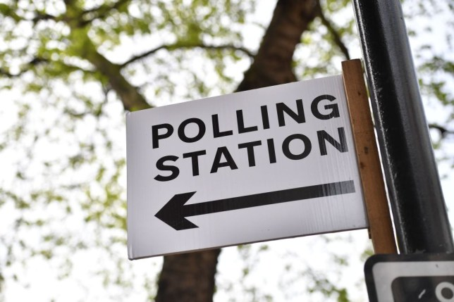 A sign saying polling station with an arrow pointing left for election voting