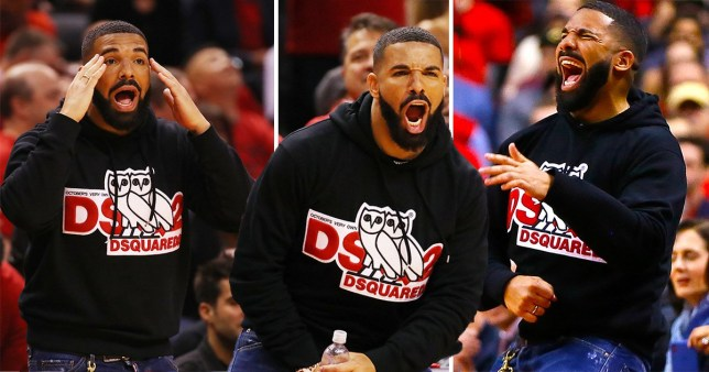 Drake reacts on NBA court side as he watches basketball.