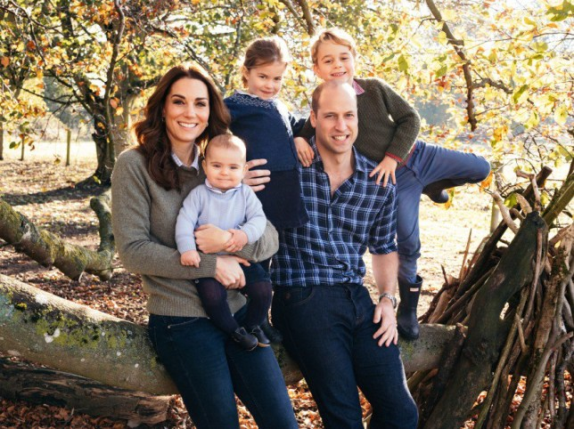 Prince William and Kate Middleton sitting on a tree log in their garden with Prince Louis, Princess Charlotte and Prince George