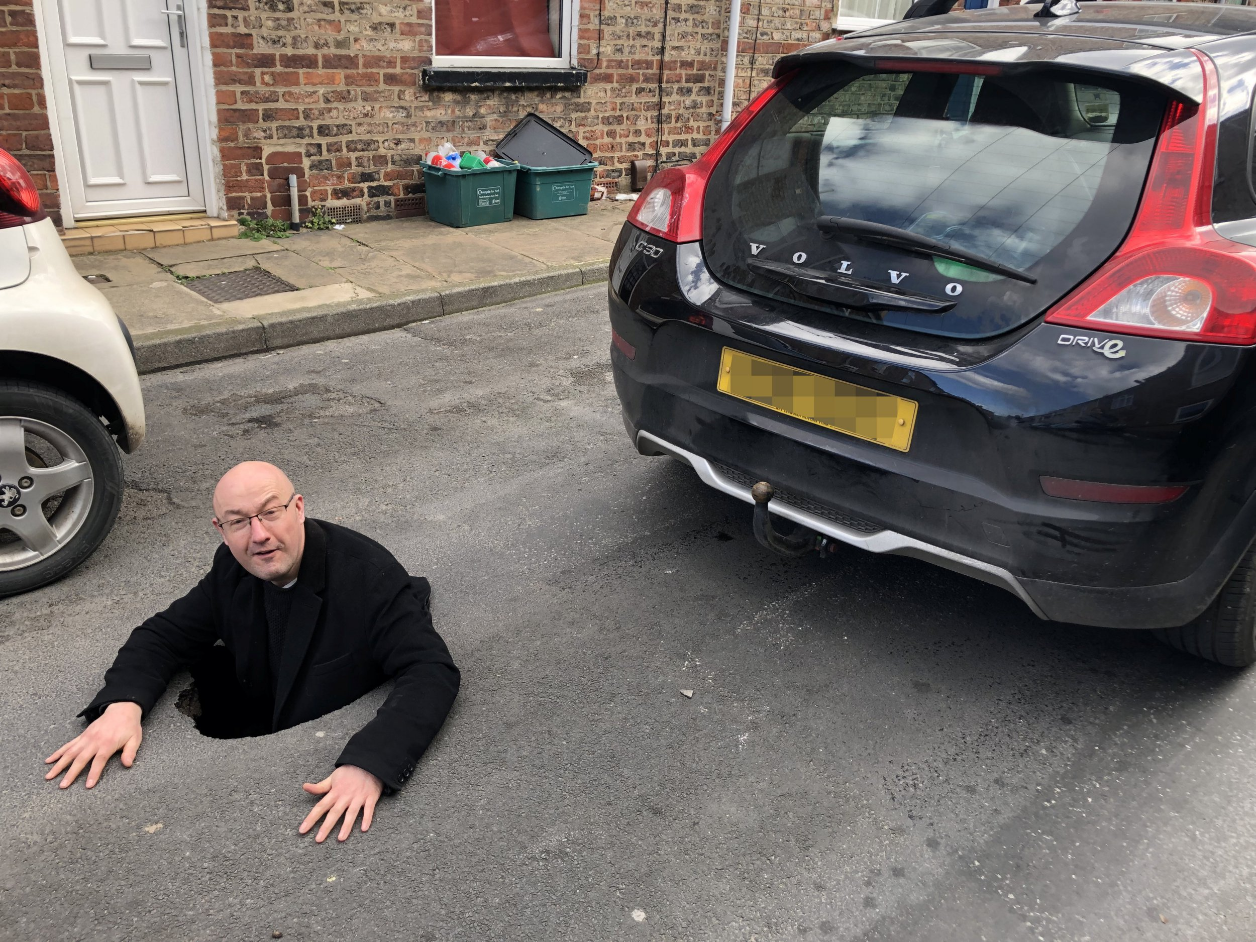 """Grant Parker in the pot hole, Grant Parker was driving his Volvo C30 in Granville Terrace, off Hull Road, York , when part of the road surface collapsed - opening up a hole in the road big enough for him to climb into. See SWNS story SWLEhole; A motorist thought """"hell had opened up"""" when his vehicle plunged into a four foot deep pothole - that was big enough for him to climb inside. stunned Grant Parker, 46, was driving down a residential road when part of the tarmac suddenly collapsed under the weight of his wheel."""