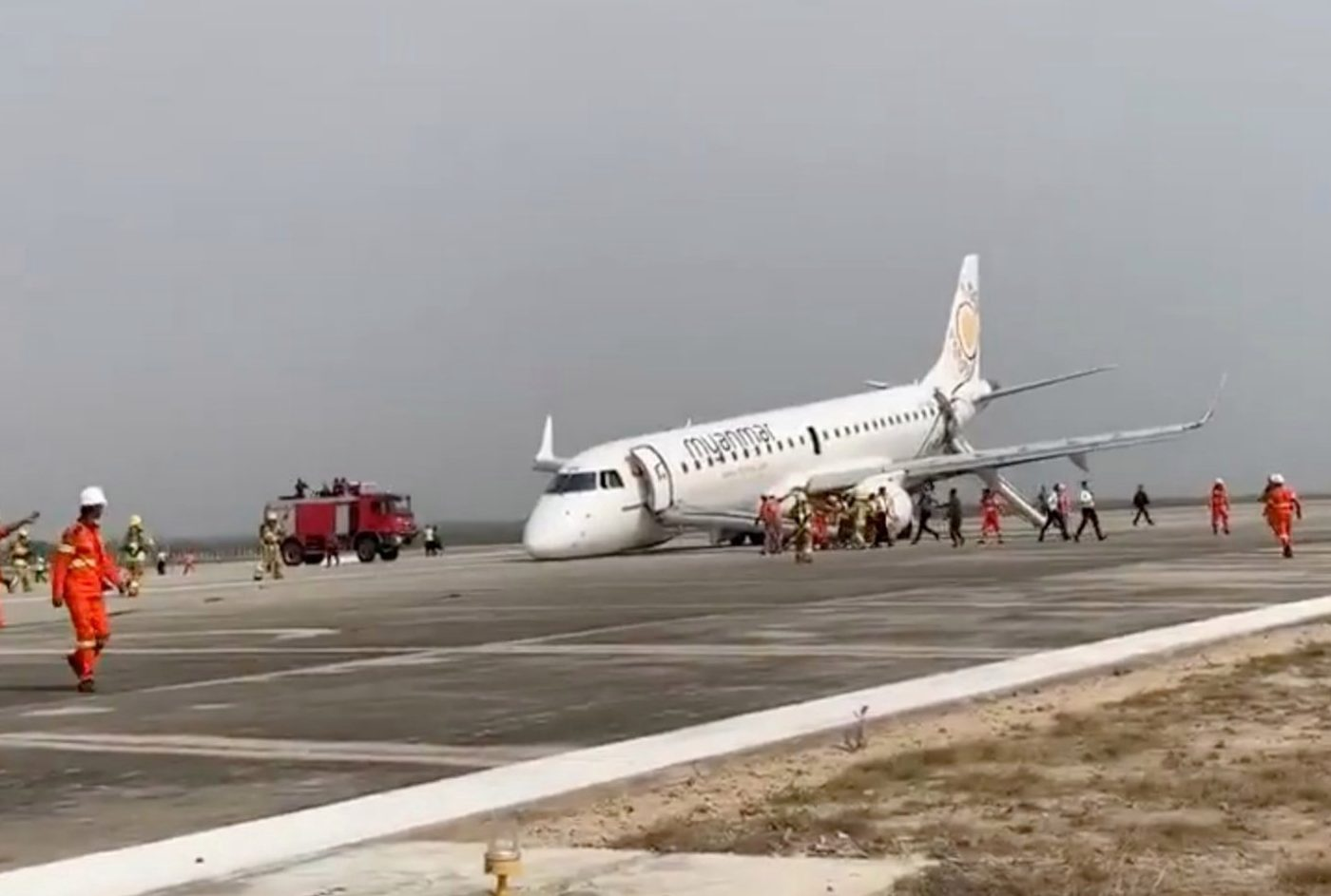 A passenger records the scene on her phone as firefighters attend to the scene after Myanmar National Airlines flight UB103 landed without a front wheel at Mandalay International Airport in Tada-U, Myanmar May 12, 2019 in this still image taken from social media video. Nay Min via REUTERS ATTENTION EDITORS - THIS IMAGE WAS PROVIDED BY A THIRD PARTY. NO RESALES. NO ARCHIVES. MANDATORY CREDIT