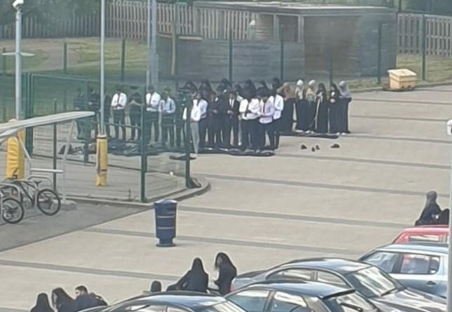 Children pray outside in the car park