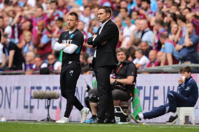 John Terry stands on the touchline next to Frank Lampard