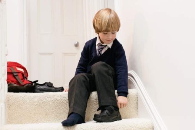 A young schoolboy in uniform puts on his new shoes ready for school