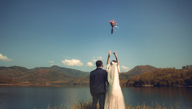 Bride and groom standing in a nature setting by a lake with hills in the background, with the bride throwing her bouquet in the air