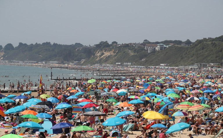 People enjoy the sunshine and hot weather on Bournemouth Beach in Dorset.