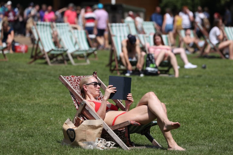 Sunbathers lie on deck chairs in Green Park, London