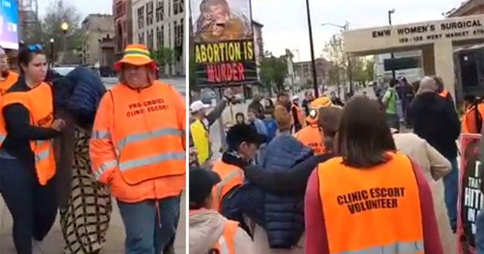 A woman covers her head to be escorted into an abortion clinic in the USA as the country rolls back reproductive rights of women