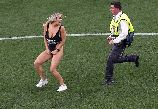 A member of the security chases a pitch invader during the UEFA Champions League final