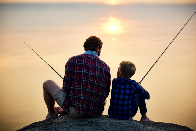 Father and son fishing at sunset