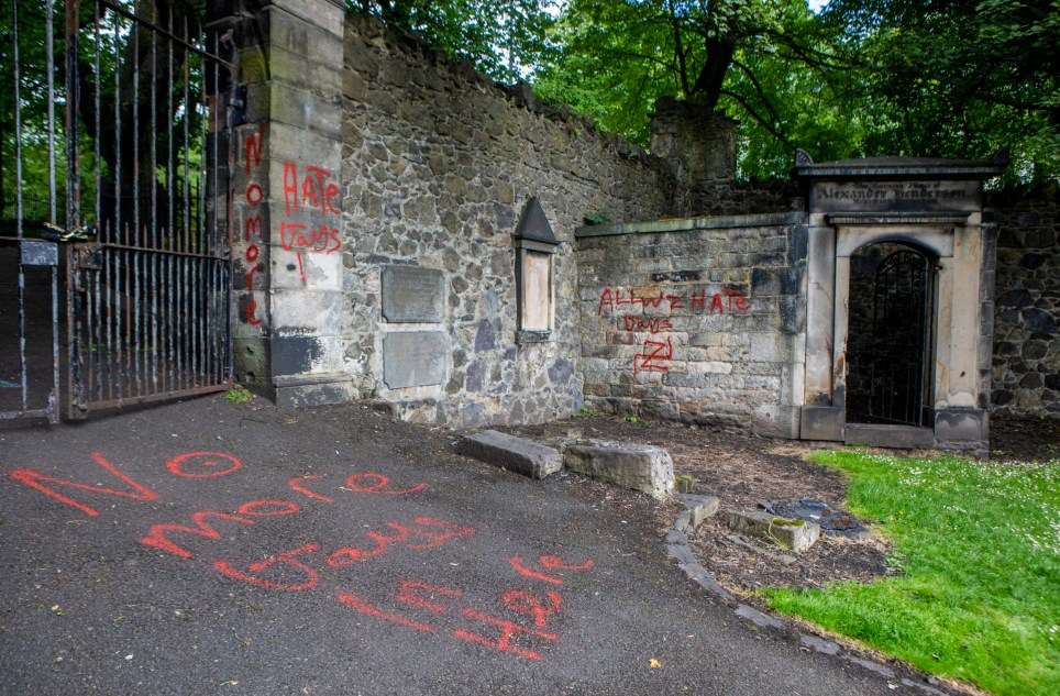 Swastikas and homophobic graffiti on tombs in New Calton Burial Ground close to the Scottish Parliament. June 17 2019 . See SWNS story SWSCgraffiti. Mindless yobs have daubed vile graffiti including swastikas on a war memorial at a historic cemetery. A tour guide with a group from New York came across the nasty work at the New Calton Burial Ground, Edinburgh. They were left horrified by the foul paintwork over the weekend at the Regent Road cemetery popular with visitors to the Capital. The crudely drawn and illiterate graffiti included the phrase; ?No more gays in here? at the entrance to the cemetery and ?always hate gays? above two swastikas on a family?s private plot.