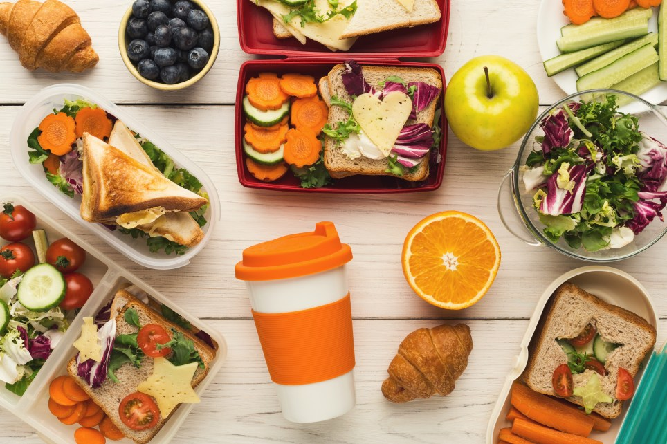 Lunch box filled with mixed vegetables salad and oatmeals. Take away coffee cup and various fruits and snacks on white wooden table background, top view