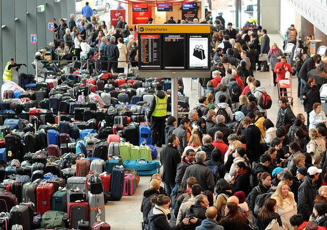 People queuing at an airport departure lounge next to rows of luggage