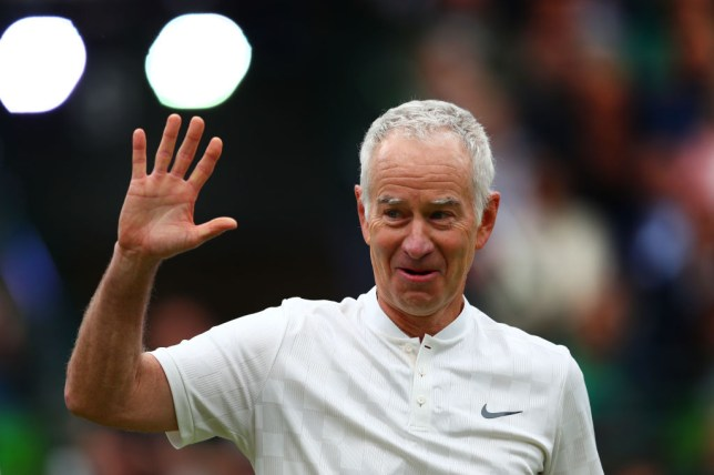 John McEnroe waves to the Wimbledon crowd