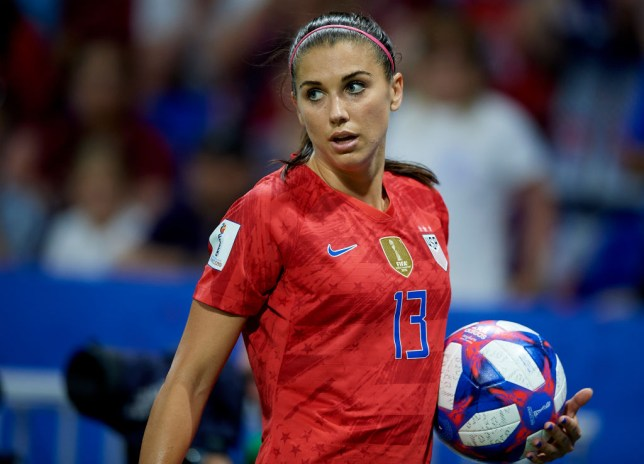 Alex Morgan holding a football on the pitch during the Women's World Cup 2019