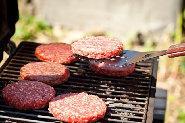 Burgers cooking on a BBQ outside