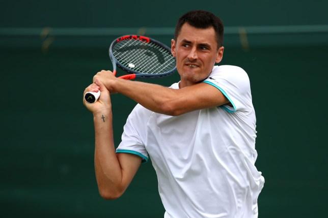 Bernard Tomic hits a backhand at Wimbledon
