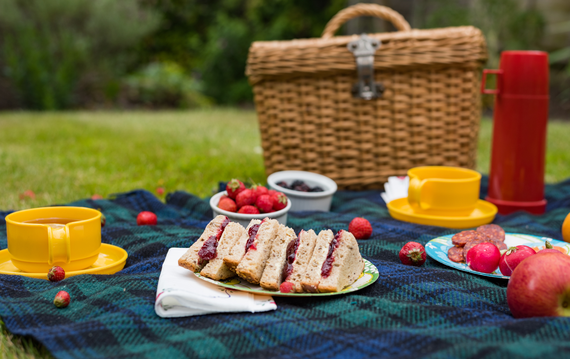 A cruise widespread in a park including jam sandwiches, fruit, a basket and a yellow crater